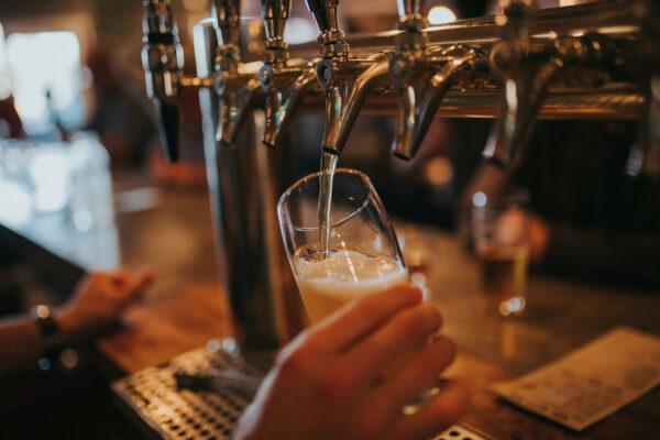 Bild på person som häller upp öl i ett ölglas i baren.